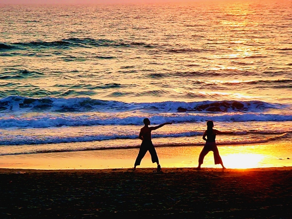 Doing exercise on beach at sunset
