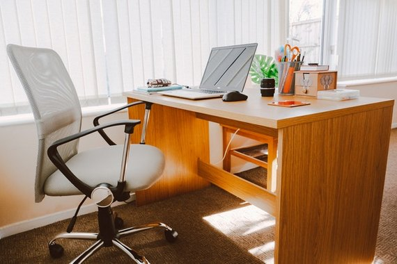 Ergonomic chair and office desk by the window to illustrate how you can make your office better for your health.