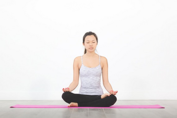 A woman sitting in yoga lotus position