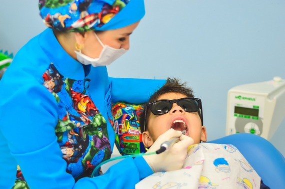 Nurse assisting child at dentist