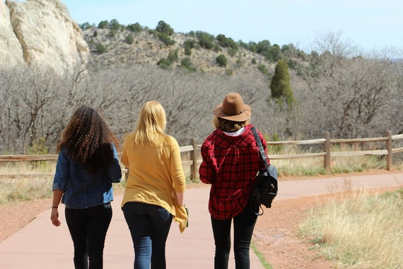 Three women friends walking in rural area